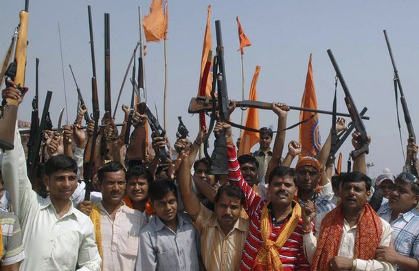 Activists of Bajrang Dal hold their weapons in Agra