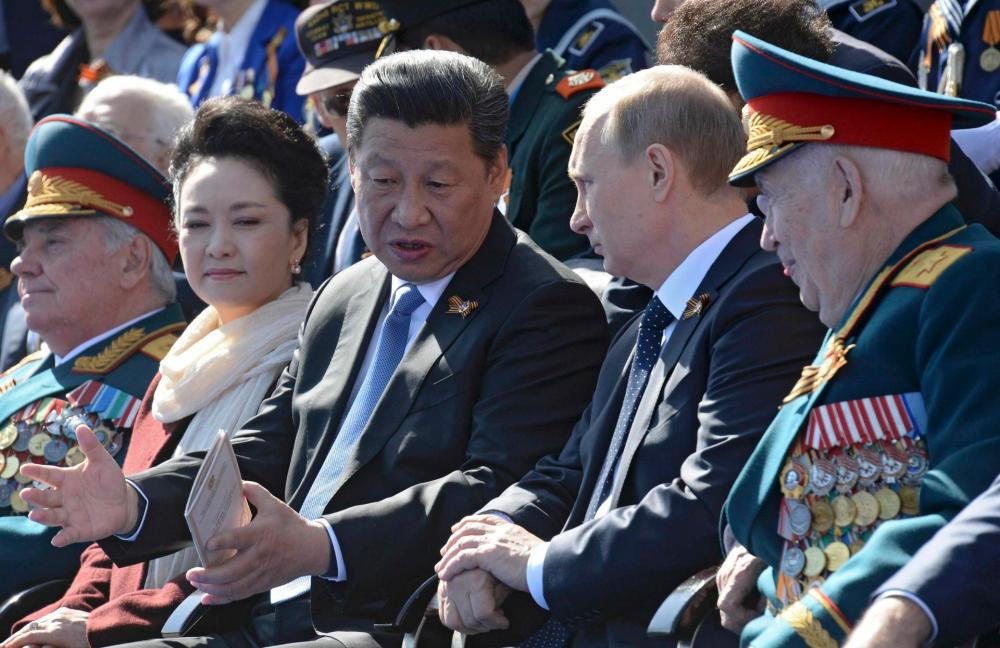 Russia's President Putin speaks with China's President Xi during the Victory Day parade at Red Square in Moscow