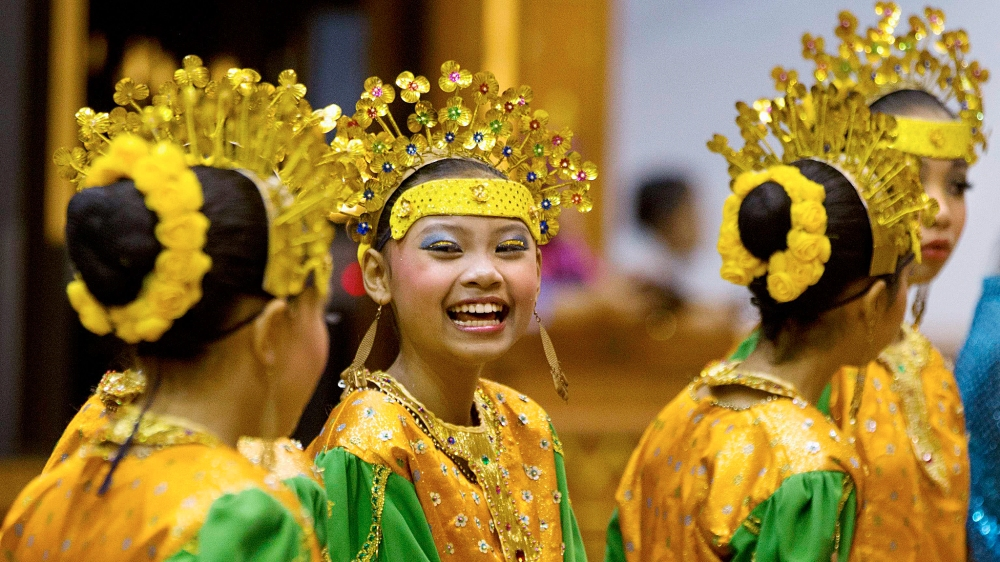 Girls in traditional costumes waits to greet foreign ministers before a cultural event at the ASEAN security conference in Bandar Seri Begawan