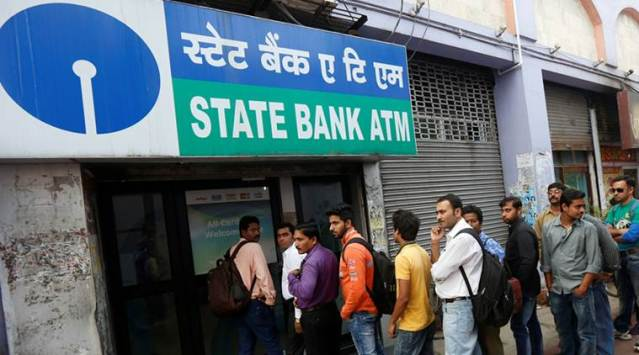 People queue outside an ATM of State Bank of India to withdraw money in Kolkata