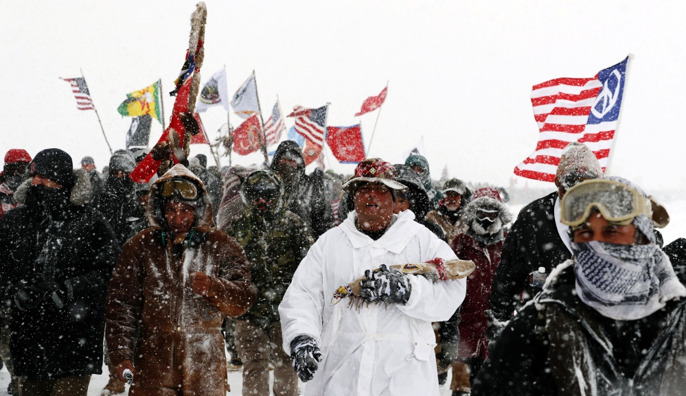 """Veterans join activists in a march to Backwater Bridge just outside the Oceti Sakowin camp during a snow fall as """"water protectors"""" continue to demonstrate against plans to pass the Dakota Access pipeline adjacent to the Standing Rock Indian Reservation"""