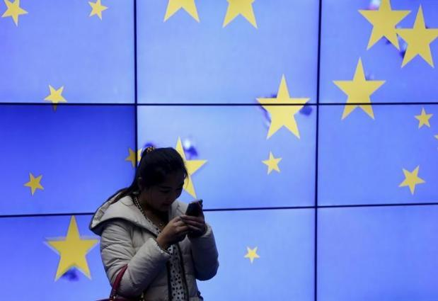 A visitor uses her mobile phone in front of an electronic board in the atrium of the European Council building in Brussels