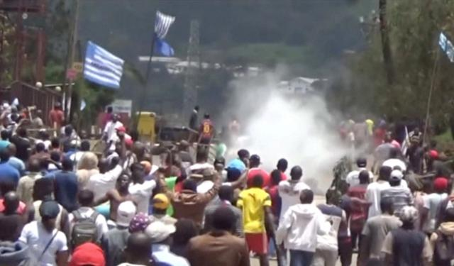 FILE PHOTO: A still image taken from a video shows protesters waving Ambazonian flags as they move forward towards barricades and police amid tear gas in the English-speaking city of Bamenda